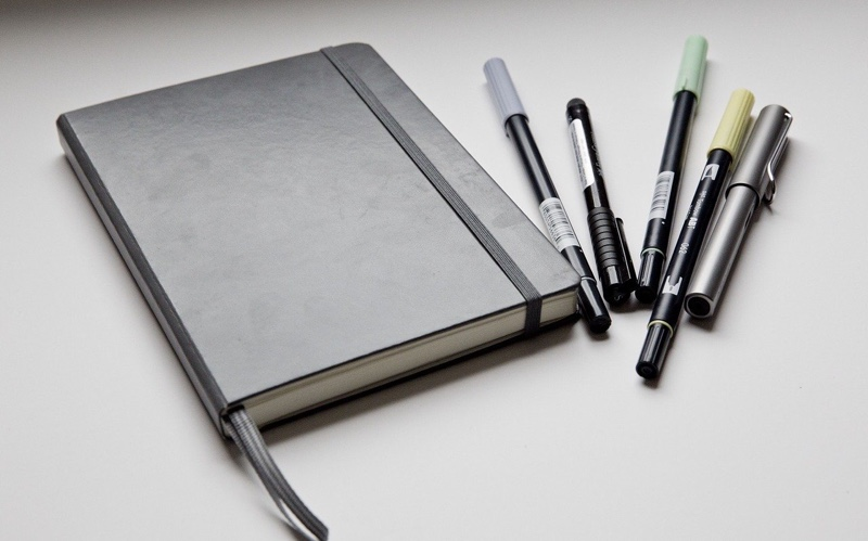 An image of a black journal and a set of pens.